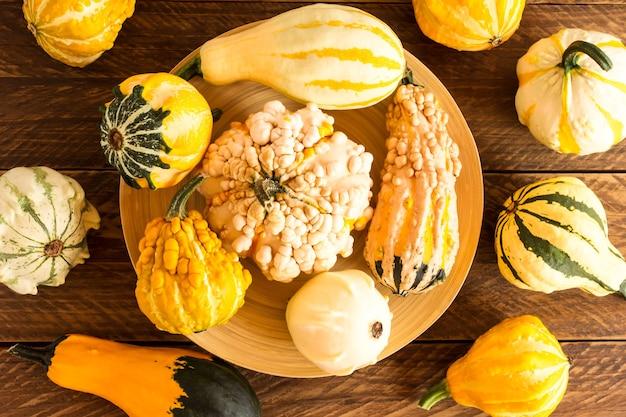 Различные декоративные тыквы на бамбуковом блюде на деревянном столе. вид сверху. осенняя композиция.