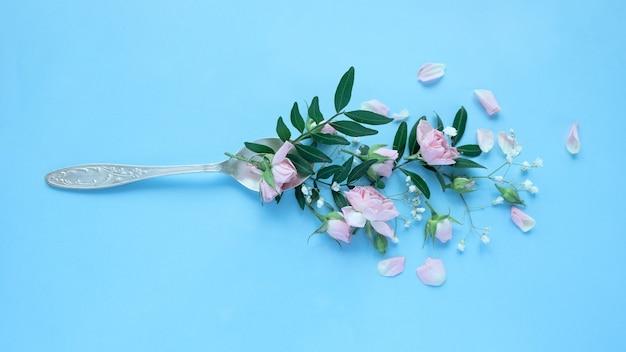 青い背景のスプーンで様々な繊細な花。アロマドリンクのコンセプト