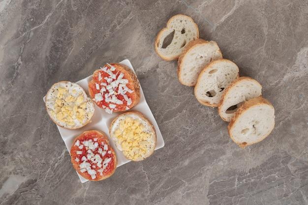 パンのスライスと白いプレート上の様々なおいしいブルスケッタ。高品質の写真