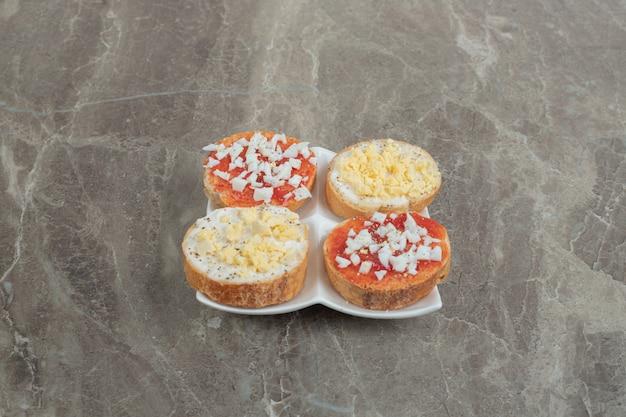 Vari deliziose bruschette sulla piastra bianca. foto di alta qualità