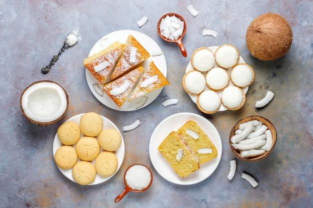 Различные вкусные кокосовые конфеты, печенье, торт, зефир, кокосовая стружка и половинка кокоса, вид сверху