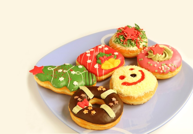 Various design of colorful christmas decorated doughnuts sweets on light blue plate
