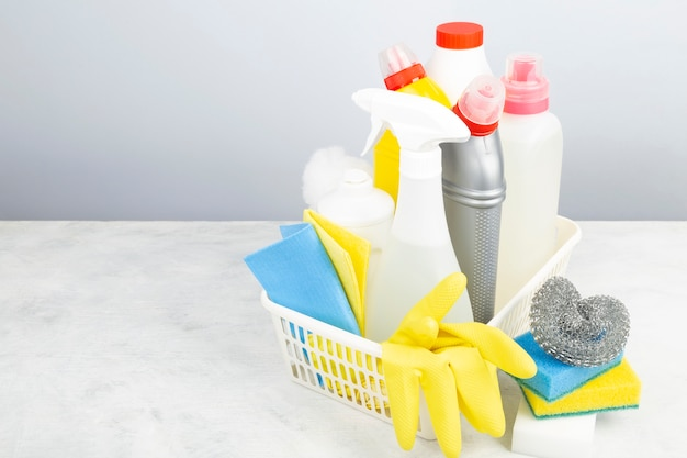 Различные моющие и чистящие средства, губки, салфетки и резиновые перчатки, серый фон. копировать пространство