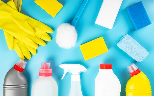 Various detergents and cleaning products agent, sponges, napkins and rubber gloves, blue background. top view