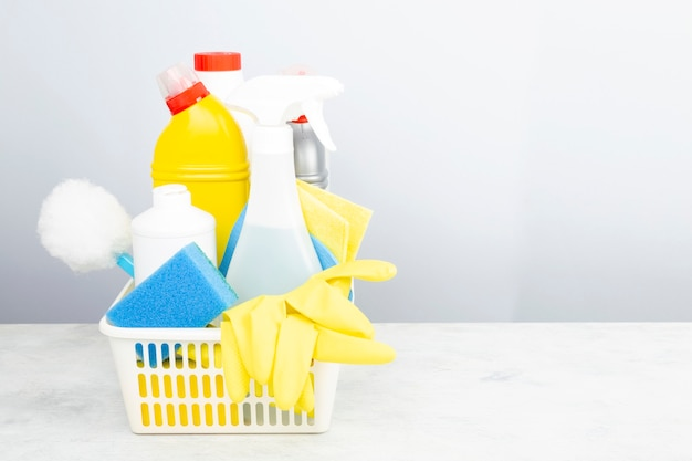 Various detergents and cleaning products agent, sponges, napkins and rubber gloves, gray background. copy space