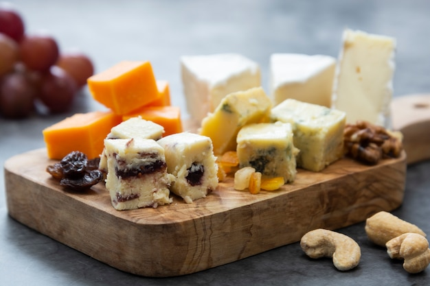 Various different types of cheese slices, cheese mix on wooden cutting board.