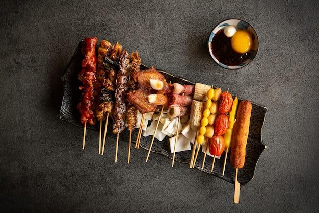 На черной тарелке размещены различные блюда и соусы. фон - серая текстура.