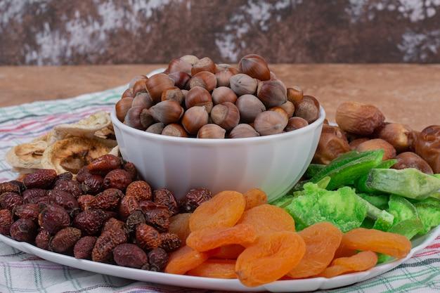 흰색 접시에 다양 한 말린 과일과 견과류입니다.