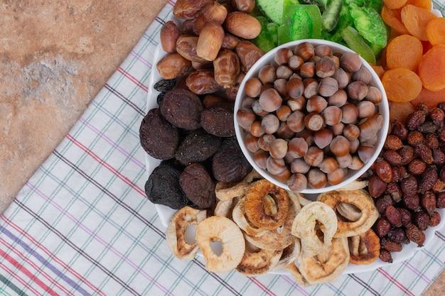 Различные сухофрукты и орехи на белой тарелке.