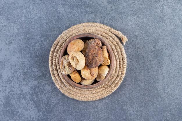 Various dried fruits in a bowl on a trivet , on the marble background.