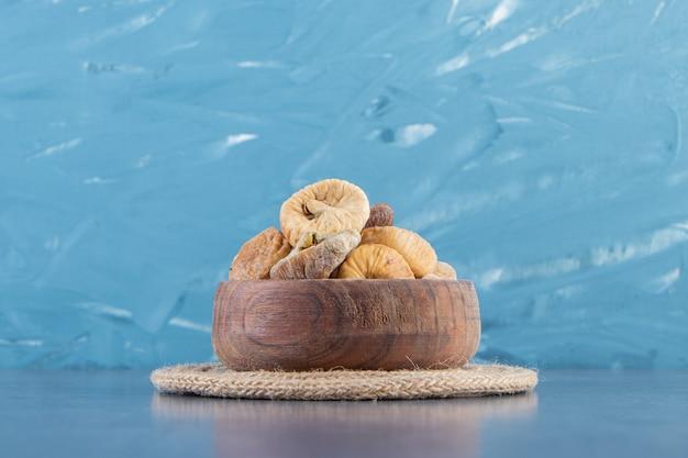 Vari frutti secchi in una ciotola su un sottopentola, sullo sfondo di marmo.