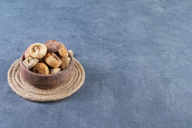 Vari frutti secchi in una ciotola su un sottopentola sulla superficie di marmo