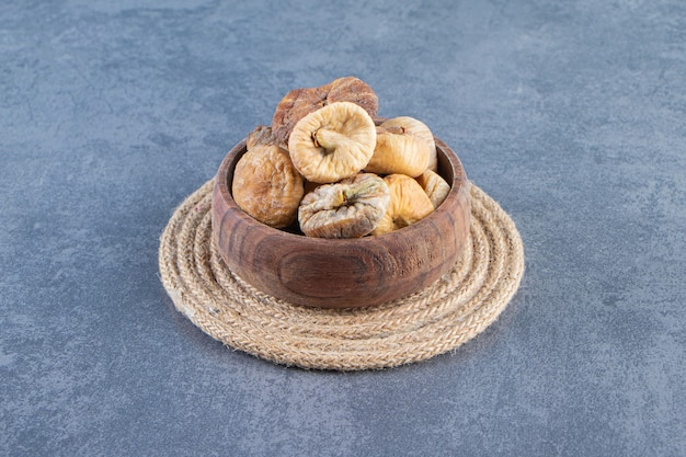 Various dried fruits in a bowl on a trivet on the marble surface