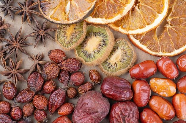 Vari frutti secchi e chiodi di garofano sul pezzo di legno.