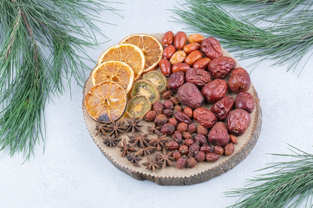 Various dried fruits and cloves on wooden piece.
