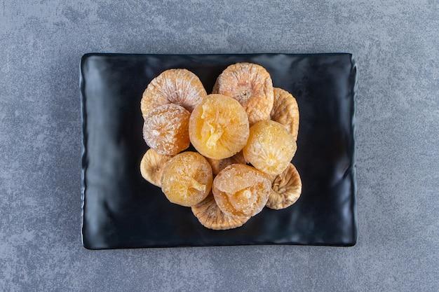 대리석 배경에 있는 트리벳에 있는 그릇에 다양한 말린 과일.
