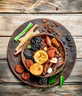 素朴なテーブルのボウルにさまざまなドライフルーツ。