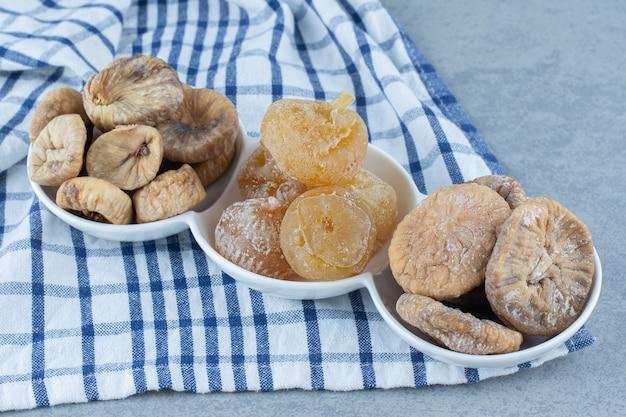 ボウル、ティータオル、大理石のテーブルにあるさまざまなドライフルーツ。