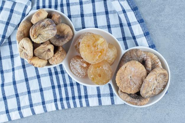 그릇에 있는 다양한 말린 과일, 차 타월, 대리석 테이블.