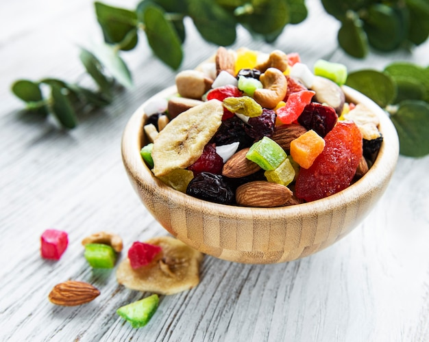 Various dried fruits and mix nuts on a white wooden  background.