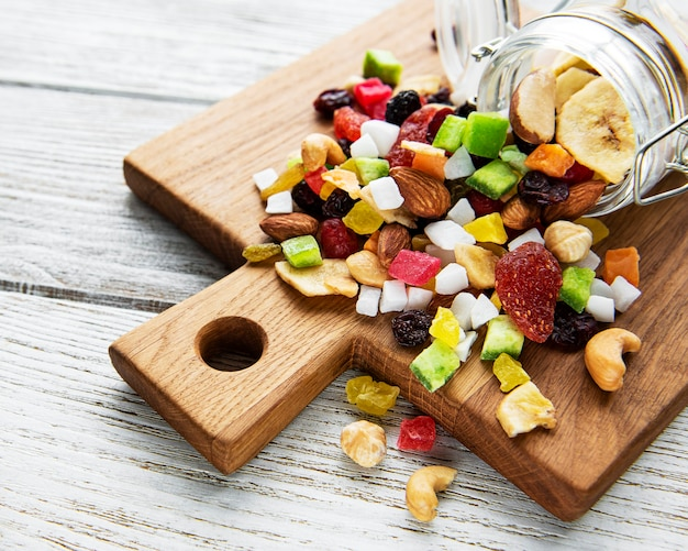 Various dried fruits and mix nuts on a white wooden surface