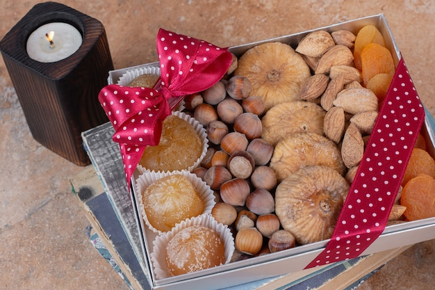 Various dried fruits and nuts on gift box.
