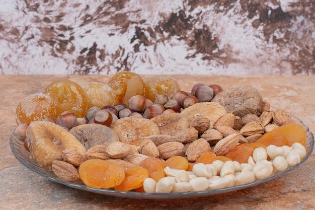 Vari frutti secchi e noci su lastra di vetro.