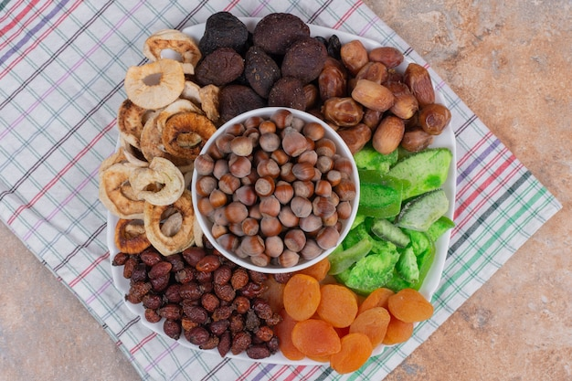 Various dried fruits and nuts on white plate.