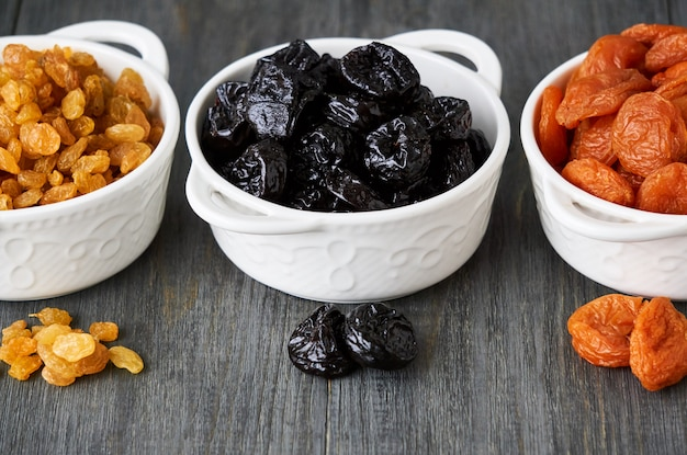 Various dried fruits in white bowls on wooden table