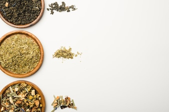 Various dried herbs on wooden plates against white background