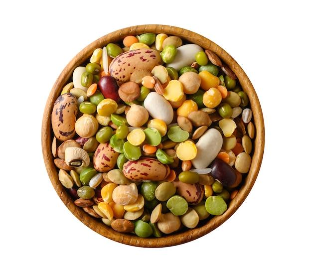 Различные сушеные бобовые: чечевица, фасоль, горох, нут в деревянной чашке, вид сверху, изолированные на белом.