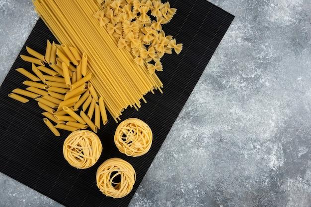 Varie pasta secca su foglio di bambù nero.