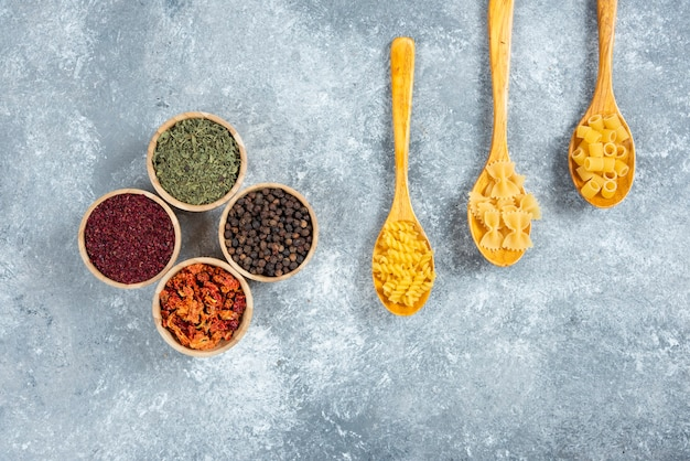 Various dry pasta and spices on marble background.