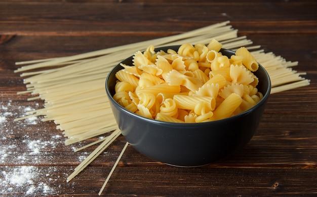 Различные сухие макароны с посыпать мукой на деревянный стол, высокий угол обзора.
