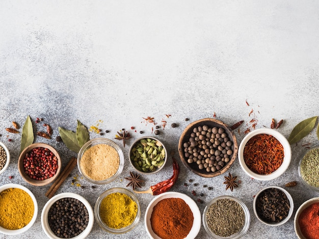 Various dry spices flat lay in small bowls on gray background. top view, copy space