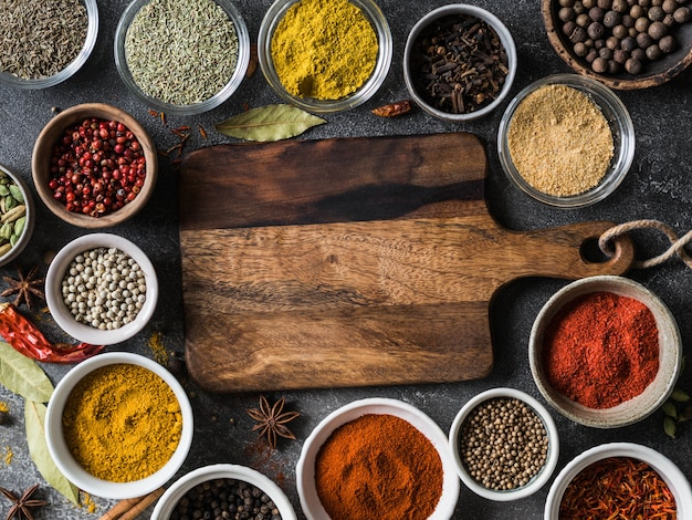 Various dry spices flat lay in small bowls and wood board on gray background. top view,