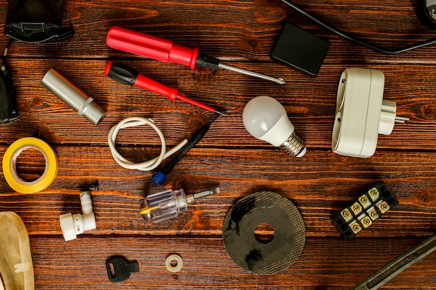 Various electrical supplies on a wooden table. repair of electrical equipment at home with your own hands. getting ready to repair the wires. high quality photo