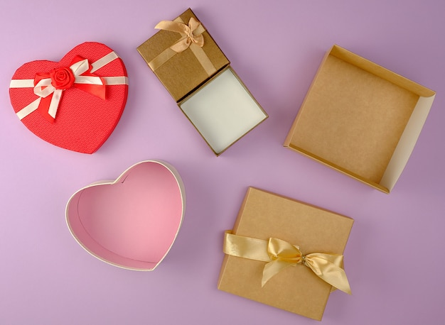 Various empty open paper gift boxes on purple background