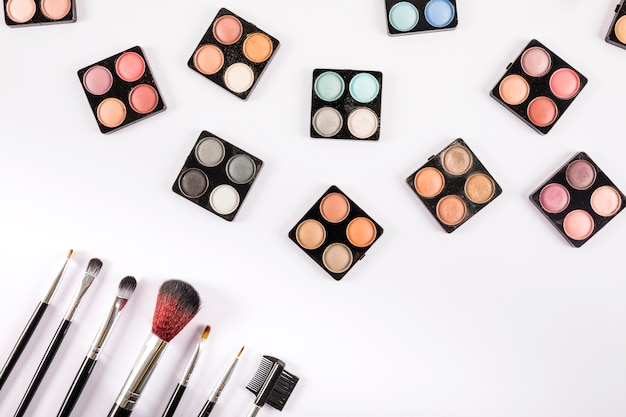 Various eye shadow powders and brushes on white background