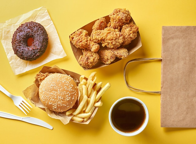 Various fast food products and paper shopping bag on yellow background, top view
