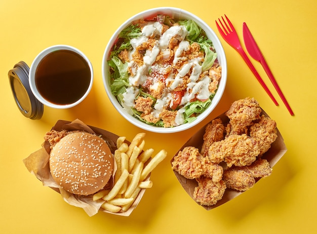 Various fast food products and on yellow paper background, top view