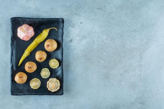 青い表面の皿にさまざまな発酵野菜