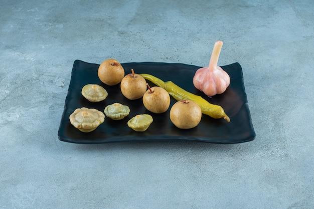 Различные ферментированные овощи на тарелке на синей поверхности