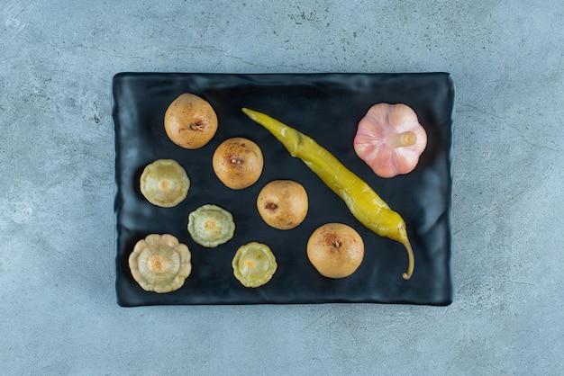 Различные ферментированные овощи на тарелке, на синем столе.
