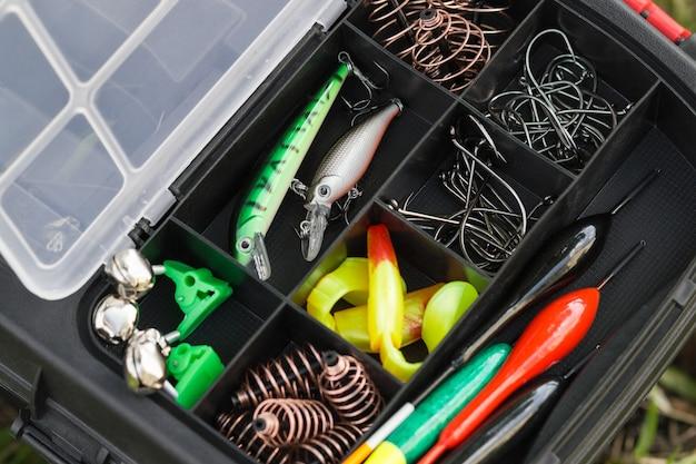 플라스틱 태클 상자에 있는 다양한 어부의 장비. 낚시와 취미 개념입니다.