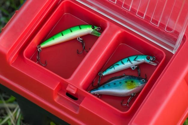 赤いタックルボックスの様々な釣りのルアーと餌。上面図。フービーとレジャーのコンセプト。
