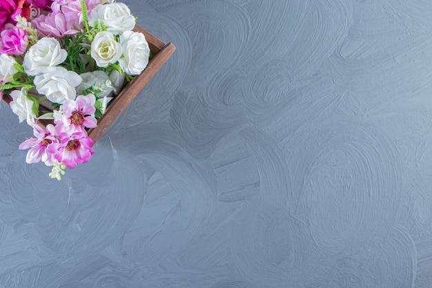 Vari fiori in una scatola, sul tavolo bianco.
