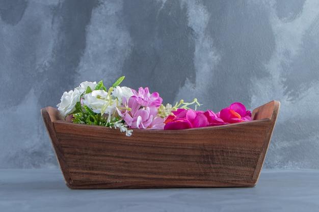 白い背景の上の箱の中の様々な花。