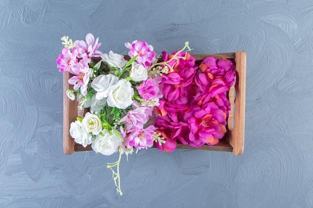 白いテーブルの上に、箱の中の様々な花。