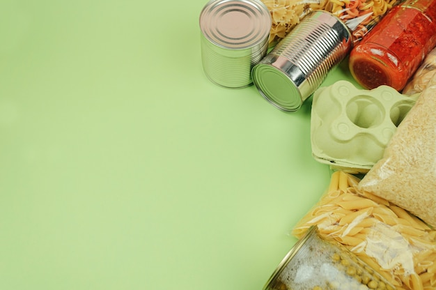 さまざまな食品が緑の背景に横たわっています。商品の購入、配送または寄付、商品の在庫